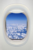 Window of an airplane from inside, view on snowy mountains Royalty Free Stock Photos