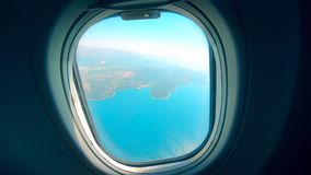 Window of an airplane with water and the land in it. HD stock video