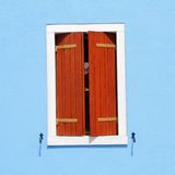 Window with ajar shutters. Detail of colorful facade with window with ajar shutters, Burano, Venice, Italy, Europe Stock Image