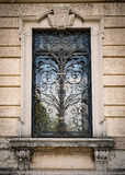 Window of an ancient Italian villa with artistic iron grill. Royalty Free Stock Photos