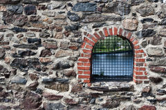 Window arc biuilt into stone wall. Stone wall fixed with cement with cracks Royalty Free Stock Photos