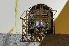 Window with a lattice, El Jadida, Morocco. Window with an arch and a dark colored wooden frame. Lattice and its shadow. Plants in the pots. Yellow and grey stock image