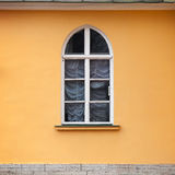 Window with arch in yellow wall Royalty Free Stock Photos