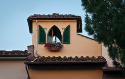 Attic in Florence. Window of attic in Florence ... Florence is full of beautiful mansarda,attic and this one with the pink  flowers and green shutters looks so Royalty Free Stock Photos