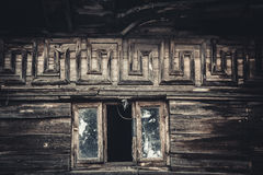 The window of the attic in an old house. Attic window in an old wooden house, ornament meander royalty free stock images