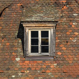 Window of attic on old tiled roof. Royalty Free Stock Images