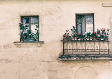 Window, balcony, flowers, fragment,  photo in old image style. Royalty Free Stock Images