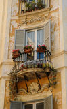 Window and balcony of a medieval italian palace. Window and balcony with flowers and plants of a medieval italian palace Stock Photos