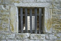 Window with bars. A window with wooden bars, in a medieval wall Stock Photo