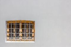 Window with bars on a gray wall Royalty Free Stock Photography