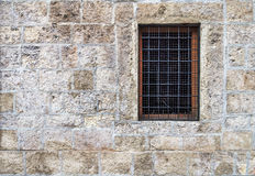 Window with bars in the old stone wall Royalty Free Stock Image