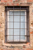 Window with bars. Very old and rugged window on brick wall with bars Stock Images