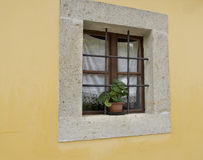 Window with bars on yellow wall Royalty Free Stock Image