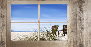 Window with Beach View. A rustic wood window frame with view of two adirondack style chairs on beach sand and view of islands in the distance