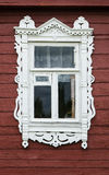 Window with beautiful fretted wooden case nasus. It`s a traditional decoration of old russian wooden houses Stock Image
