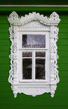 Window with beautiful fretted wooden case nasus. It`s a traditional decoration of old russian wooden houses Royalty Free Stock Photo