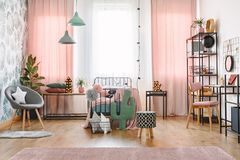 Window and bed in bedroom. Big window with pink curtains, pompoms, star and cactus pillows and a metal single bed in a sweet bedroom interior stock photos