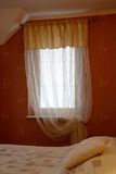 Window In Bedroom. Portrait format shot of a bedroom window, including surrounding wallpaper and partial view of bed royalty free stock photos