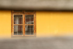 Voyeur. Old wooden window on a yellow wall behind fences Stock Images