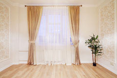 Window with beige curtains in simple room Stock Photography