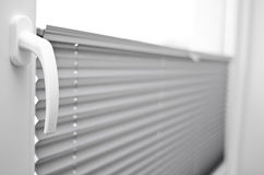 Window blinds. Modern window vertical blinds detail with the handle focused stock image
