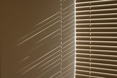 Window blinds. Sunshine patterns on the wall casted by window blinds Stock Photos