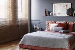 Window blinds in a bedroom interior with a king size bed, cushions, painting and vases stock images