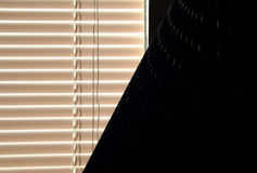 Window blinds and lamp shade. Window blinds and a lamp shade in a dark room Stock Photos