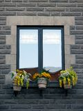 Window with blooming yellow flowers. Window of an old stone house, decorated with flowers stock photography