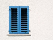 Window with blue shutters. Modern window with closed blue shutters in white rendered wall Royalty Free Stock Photo