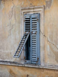 Window with blue shutters. Old window with blue shutters pictured from aside stock photo