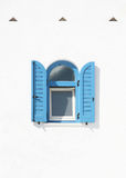 Window with blue shutters on a white wall Royalty Free Stock Image