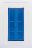 Window with blue shutters on a white wall Royalty Free Stock Photos
