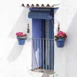 Window with blue shutters in a white whitewashed Stock Photo