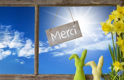 Window, Blue Sky, Merci Means Thank You. Sign With French Text Merci Means Thank You. Window Frame With View To Beautiful Sunny Blue Sky. Easter Bunny And Royalty Free Stock Photos
