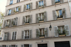 Window boxes were installed on the edge of the windows of a building in Paris (France) Stock Photography