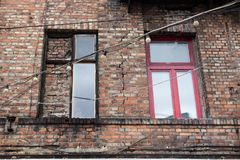 Window on the brick facade of an old house with hanging lights o. N wires Stock Image