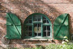 Window in a brick farmhouse with shutters in Schleswig Holstein, Germany.  royalty free stock photography