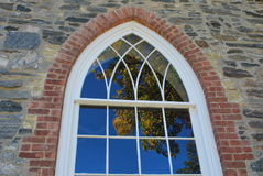 Window with brick and stone. An old church window with red brick and grey stone, with a reflection of a tree in the glass Stock Image