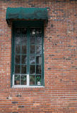 Window on Brick Wall. Old style wooden framed window on a brick wall with awning Stock Photo