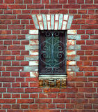 Window in brick wall. Skillful framing of window hole. Wrought iron grille curly stock image