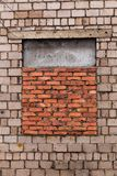 The window is bricked up. Window is laid brick. Gray brick wall with a window laid with red brick. The window is half-closed stock photo