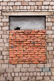 The window is bricked up. Window is laid brick. Gray brick wall with a window laid with red brick. The window is half-closed stock photography