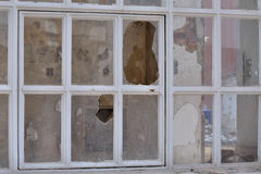 Broken glass. Window with broken glass of an abandoned building with the first signs of demolition Royalty Free Stock Photos