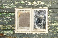 Broken window in weathered wooden facade. Window with broken glass, closed with plastic and plywood; in a wooden facade with peeling green paint stock photos