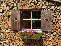 Window built in stack of wood. A window built into a stack of well-seasoned firewood - a decorative idea during storage Royalty Free Stock Photography