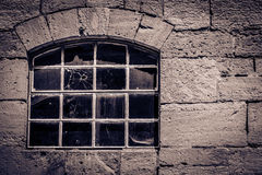 Window with Bullet Hole. Ancient window in a stone cottage with a bullet hole in the glass Royalty Free Stock Image