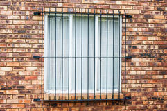 Window with Burglar Bars. On face brick wall of a house Royalty Free Stock Image