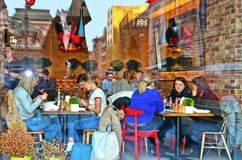 The window of a cafe bar full of people in the central area of Belgrade with glass reflections of old buildings. Serb royalty free stock images