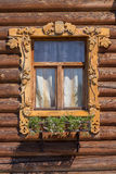 Window with carved architraves. Decorative window trim on the log wall Royalty Free Stock Photo